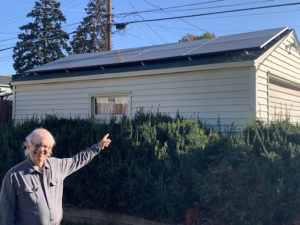 Rev. Lee Schaefer pointing to his garage, which was installed with an 8-panel solar array
